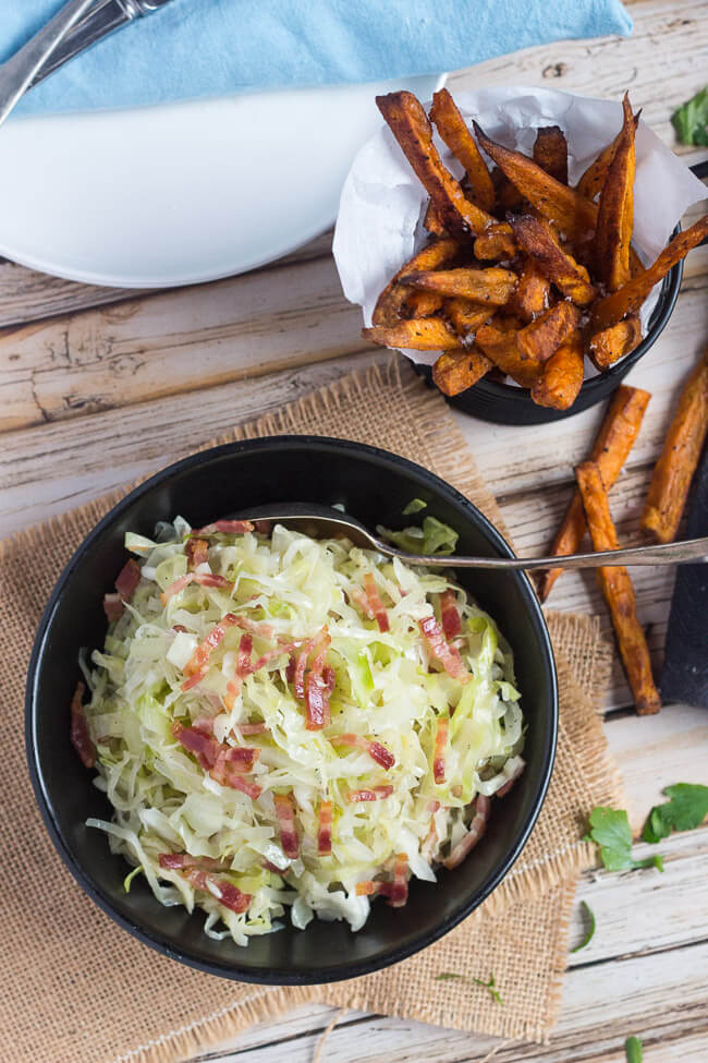 Overhead shot of a bowl of fried cabbage with bacon, and a basket of crispy sweet potato chips.