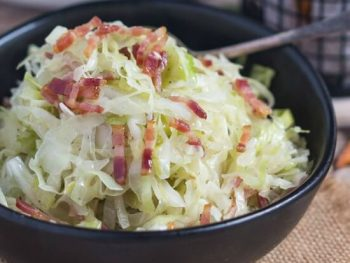 A black bowl of fried cabbage with bacon.
