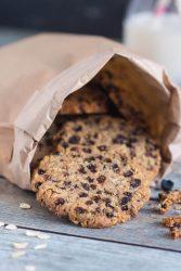 Close up shot of currant & cocoa nib cookies in a brown paper bag.
