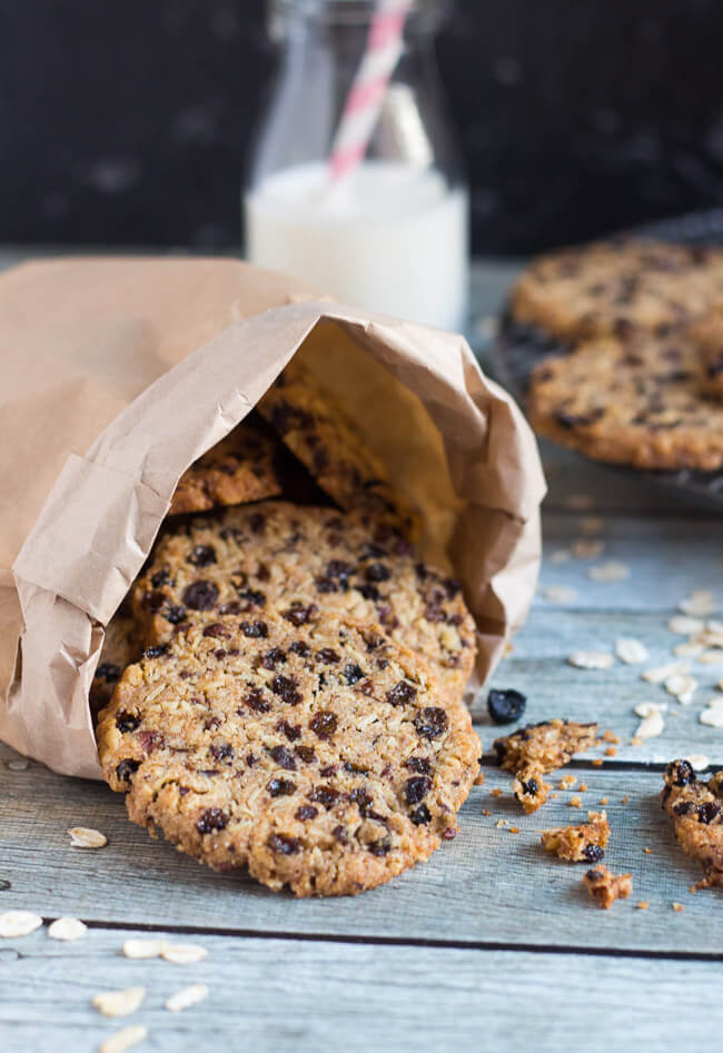 Currant & cocoa nib wholegrain cookies in a brown bag, with a bottle of milk.