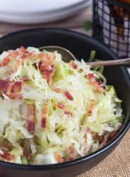 A close up shot of fried cabbage with bacon in a black bowl.