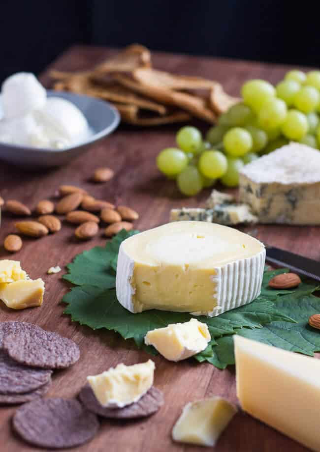 A soft rind cheese, sitting on a grape leaf, surrounded by a cut blue cheese, a fresh burrata, crackers, nuts and grapes.