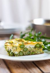 A slice of asparagus and goat cheese frittata on a white plate.