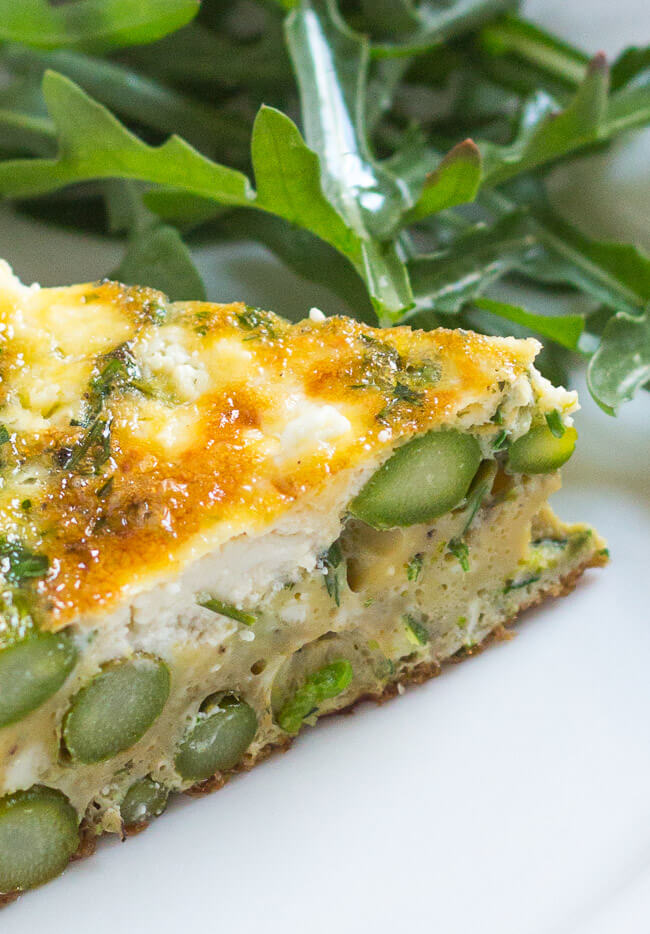 A close up shot of a slice of asparagus & goat cheese frittata on a white plate.