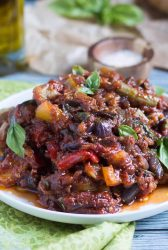 A large pile of baked ratatouille recipe on a flat white plate, with a wooden salt bowl in the background.