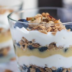 A close up shot of a layered blueberry lime curd breakfast parfait in a glass, with the distinct layers visible.