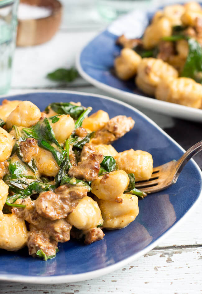 A silver fork digging into a pile of chorizo & creamy spinach easy gnocchi recipe on a blue plate.