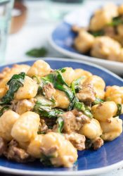 A shot of chorizo & creamy spinach easy gnocchi recipe on a blue plate, with a green water glass in the background.