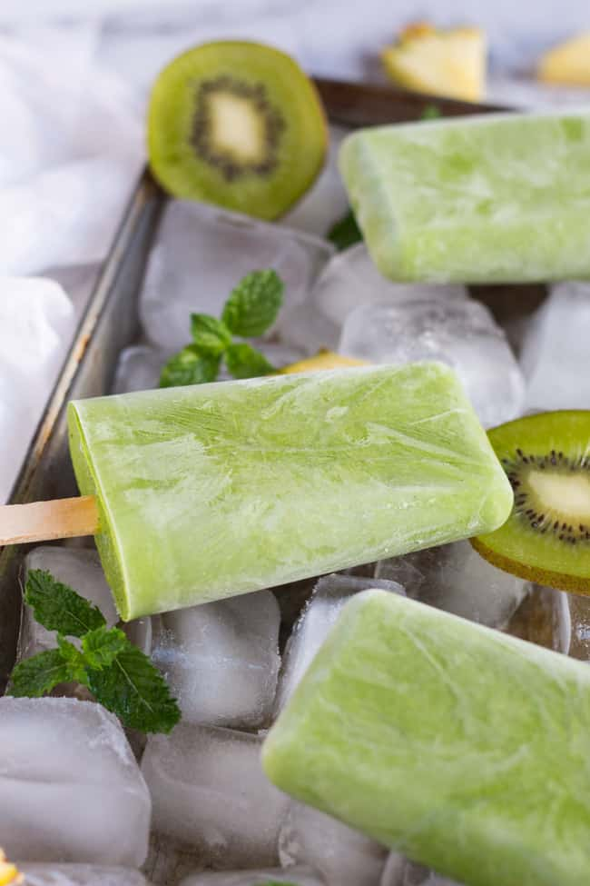 A close up shot of a green smoothie popsicle, lying on a bed of ice with slices of kiwi fruit and springs of mint.
