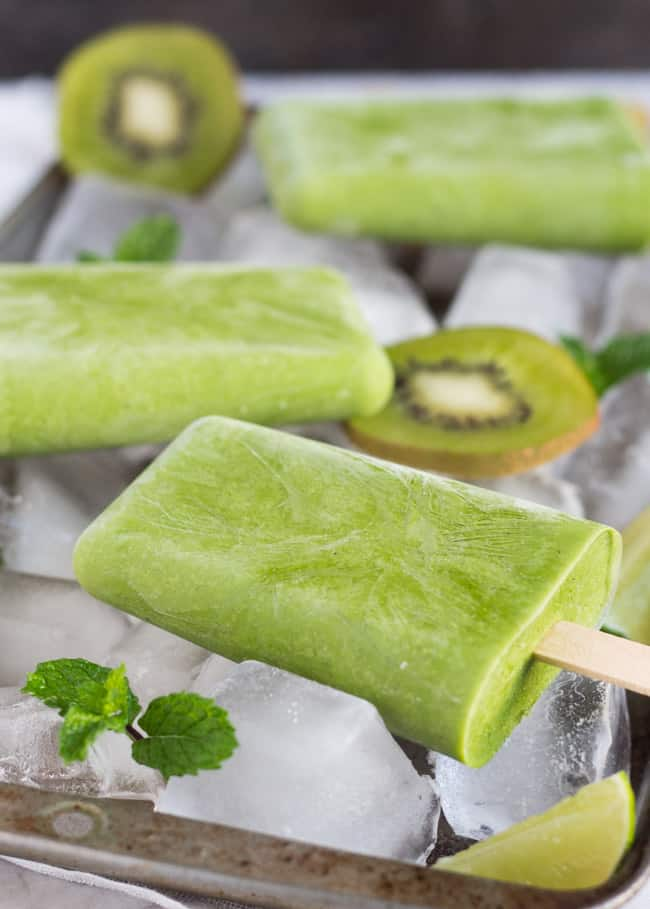 Three green smoothie popsicles on a baking tray filled with ice.