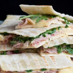 A pile of ham & brie flatbread sandwiches, with molten cheese oozing down the pile.