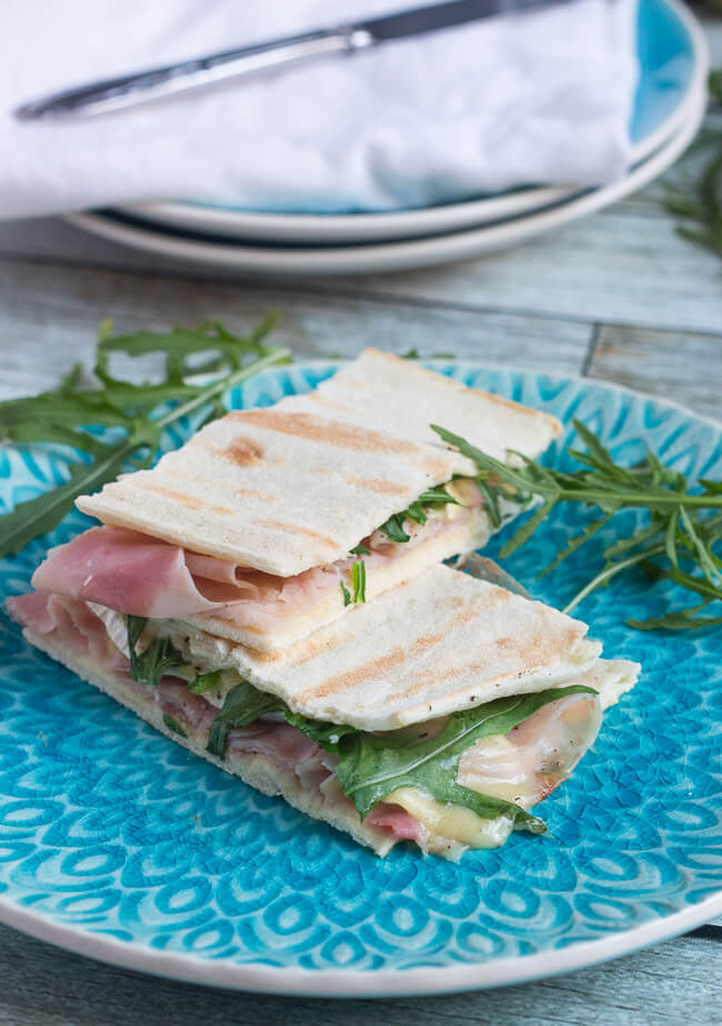 Two ham & brie flatbread sandwiches on a blue plate.