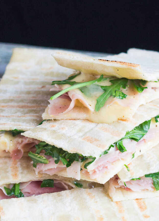 A close up shot of ham & brie flatbread sandwiches, clearly showing the flatbread filling.