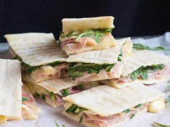 A pile of ham & brie flatbread sandwiches, with brie oozing from the sides.