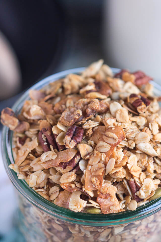A close up shot of the homemade crunchy granola recipe, showing the cooked coconut flakes, crunchy nuts and rolled oats.