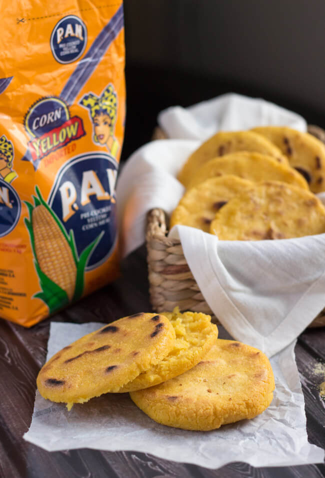 A split arepa, with a bag of Pan flour and a basket of cooked arepas in the background.
