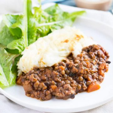 Cropped image of a single serve of lamb & lentil shpeherd's pie on a white plate.