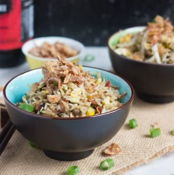 A brown bowl, with blue interior, full of fried rice and scattered with crispy fried onions.