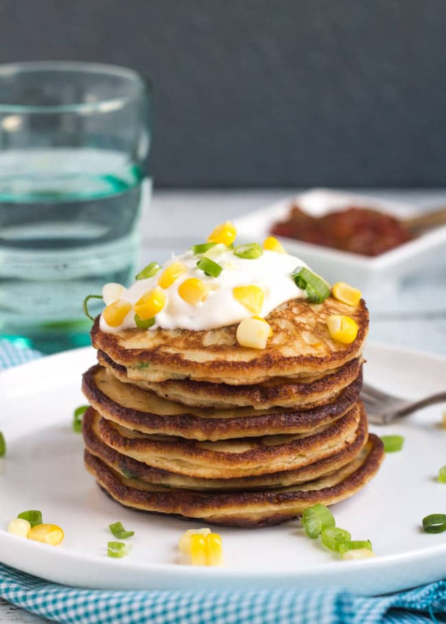 A stack of leftover mashed potato & corn pancakes, with a dollop of sour cream on top, sitting on a white plate.