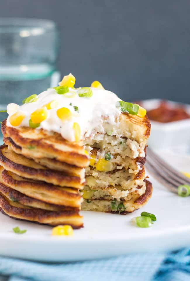 A cut stack of Leftover Mashed Potato & Corn Pancakes on a white plate, showing the fluffy interior of the pancakes.