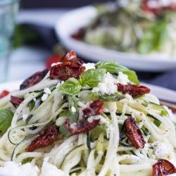 A pile of zucchini noodles, topped with oven dried tomatoes, basil leaves and crumbles of feta on a white plate.