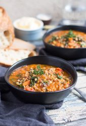 Two bowls of hearty lentil and brown rice soup recipe, with a loaf of bread and pot of butter in the background.