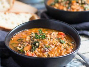 Hearty lentils and brown rice soup recipe in two black bowls.