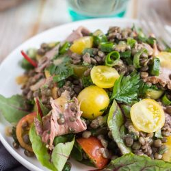 Cold roast beef salad recipe, with yellow tomatoes, beetroot leaves and green lentils on a white plate.