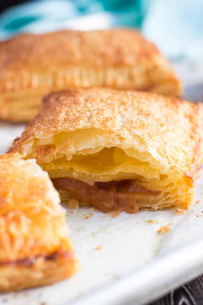 A close up shot of a cut apple turnover, made from an easy apple turnovers recipe, showing the applesauce filling and the flaky layers of the cooked filling.