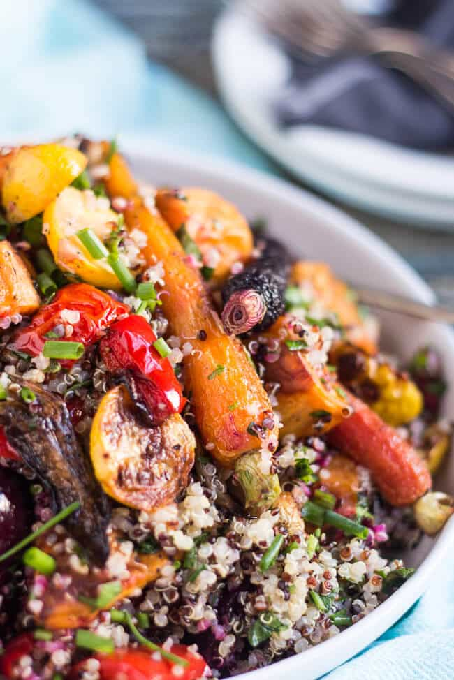 A close up shot of a bowl of Mediterranean quinoa salad, clearly showing the roasted carrots and roasted squash in the salad.