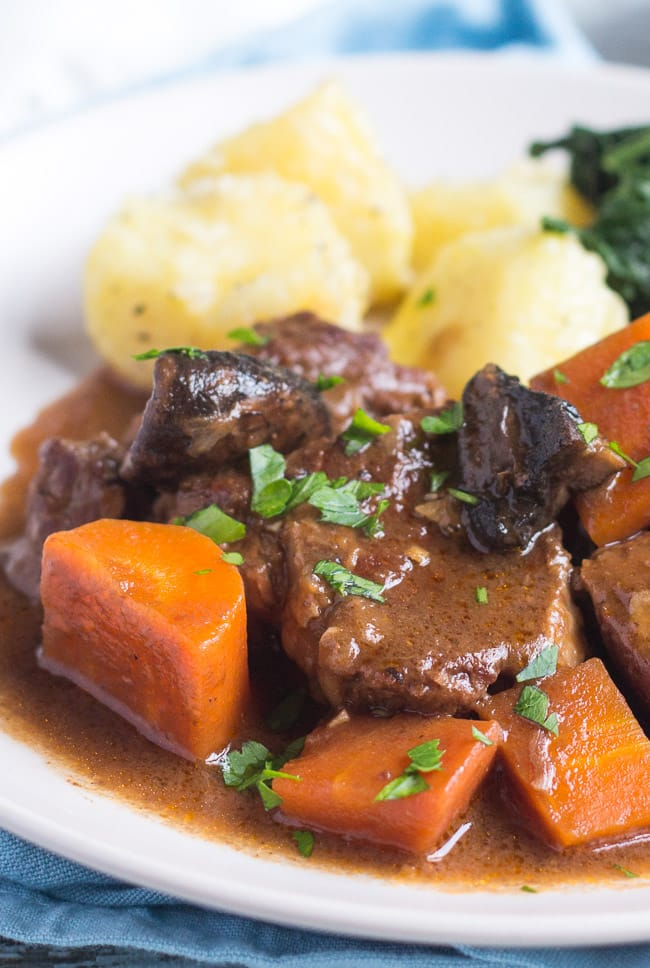 Large chunks of beef and carrot from a slow cooker beef and mushroom stew, served on a white plate with steamed potatoes and wilted spinach.