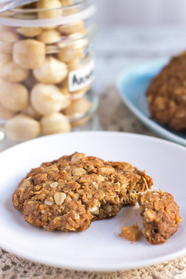 A broken healthy Anzac biscuit on a white plate.