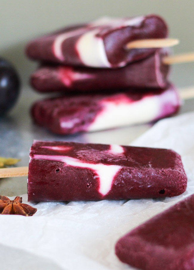 A single spiced plum & yoghurt popsicle on a sheet of baking paper, with a stack of yoghurt popsicles in the background.