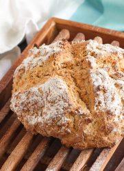 A close shot of a loaf of traditional Irish soda bread on a bread board.